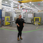 Woman posing inside manufacturing facility