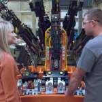 Two people in front of machinery at a manufacturing facility